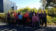 Familiengruppe schneidet Büsche am Kletterzentrum